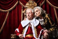 Senior woman sitting in vintage chair. Senior men in red cloak in sitting in vintage chair with beautiful senior women nearby Stock Photo