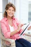 Senior woman sketching. Smiling at camera Stock Images