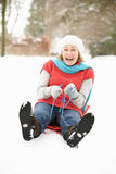 Senior Woman Sledging Through Snowy Woodland stock photo