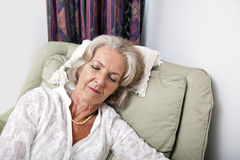 Senior woman sleeping on armchair at home Royalty Free Stock Photo