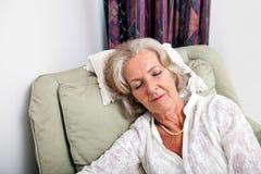Senior woman sleeping on armchair at home Royalty Free Stock Image