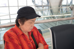 Senior woman sleeping on a chair at the airport Royalty Free Stock Photo