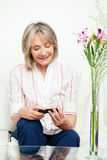 Senior woman with smartphone. Smiling senior woman sitting on couch with smartphone Stock Images