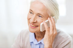 Senior woman with smartphone calling at home Royalty Free Stock Photo