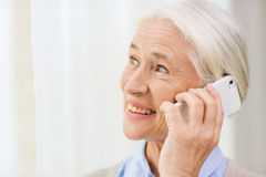 Senior woman with smartphone calling at home Stock Photos