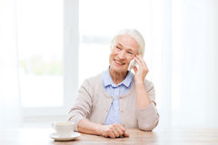 Senior woman with smartphone calling at home Stock Photography