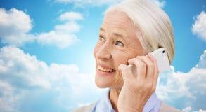 Senior woman with smartphone calling Stock Photo