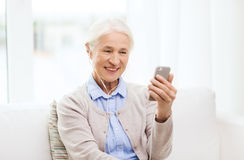 Senior woman with smartphone and earphones at home Stock Image