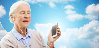 Senior woman with smartphone and earphones at home Royalty Free Stock Photography