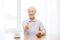 Senior woman with smartphone showing thumbs up Stock Photography