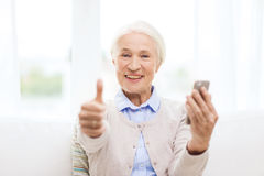 Senior woman with smartphone showing thumbs up Stock Images