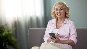 Senior woman with smartphone smiling in camera, online banking, financial app