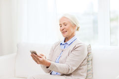 Senior woman with smartphone texting at home Royalty Free Stock Images