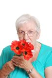 Senior woman smelling fake red poppies Stock Images