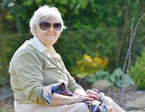 Senior woman smiling and dreaming in garden. Royalty Free Stock Images