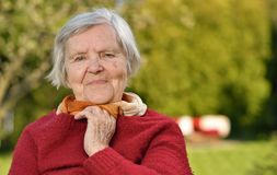 Senior woman smiling and dreaming in garden. Royalty Free Stock Photos