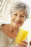 Senior Woman Smiling And Drinking Orange Juice Stock Photography
