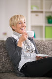 Senior woman smiling and drinking tea Royalty Free Stock Images