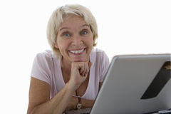 senior woman smiling by laptop computer, cut out Stock Photos