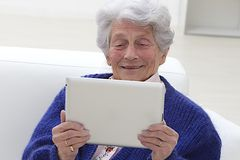 Senior woman smiling and looking to her laptop Stock Photos