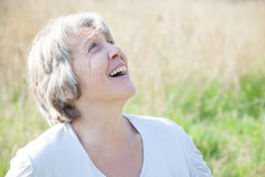 Senior woman smiling while looking up Royalty Free Stock Photos