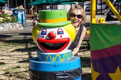 Senior woman smiling next to clown trash can. Senior woman having fun & smiling next to clown trash can Stock Photos