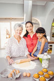 Senior woman smiling while preparing food with family Stock Photos