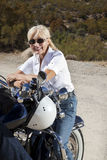 Senior woman smiling and sitting on motorcycle in desert Stock Image