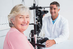 Senior woman smiling while sitting with optician Stock Image