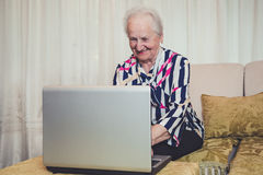 Senior woman smiling and using laptop Stock Photo