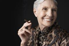 Senior Woman Smoking Cigarillo Stock Image