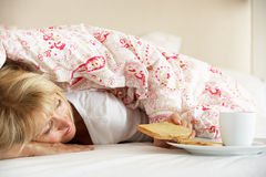 Senior Woman Snuggled Under Duvet Eating Breakfast Royalty Free Stock Photos