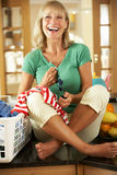 Senior Woman Sorting Laundry In Kitchen Stock Photo