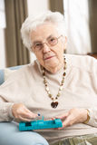 Senior Woman Sorting Medication Using Organiser. At Home Royalty Free Stock Images