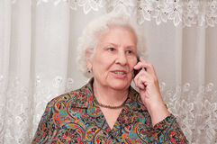 Senior woman speaks on the mobile phone Royalty Free Stock Image