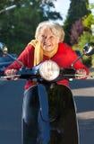 Senior woman speeding on a scooter Stock Image