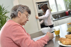 Senior woman spending time doing crosswords with a home helper in the background Royalty Free Stock Photos
