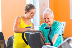 Senior woman spinning on bike in fitness gym club Royalty Free Stock Photo