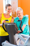 Senior woman spinning on bike in fitness gym club Stock Photo
