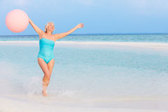 Senior Woman Splashing In Beautiful Sea Holding Balloon Royalty Free Stock Photo