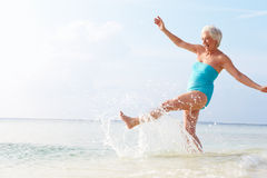 Senior Woman Splashing In Sea On Beach Holiday Stock Photos