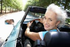 Senior woman in sports car. Smiling at camera Stock Image