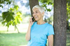 Senior woman in sports clothing  using smart phone outdoor royalty free stock photo