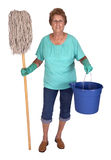 Senior Woman Spring Cleaning Lady Household Chores. Mature senior woman with mop and bucket ready to do spring cleaning and household chores. Lady is smiling as stock photo