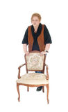 Senior woman standing on armchair. Royalty Free Stock Photography