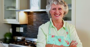 Senior woman standing with arms crossed in kitchen 4k
