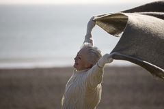 A senior woman standing on the beach, holding a blanket into the wind Royalty Free Stock Photos