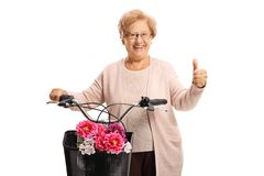 Senior woman standing with a bicycle and giving thumbs up stock images