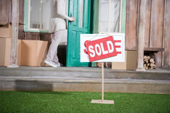 Senior woman standing in doorway of new house near sold sign on grass Stock Image