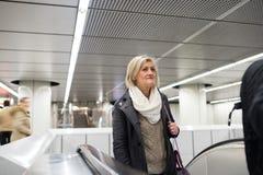 Senior woman standing at the escalator in Vienna subway. Beautiful senior woman in black coat and white woolen scarf standing at the escalator in Vienna subway Stock Image